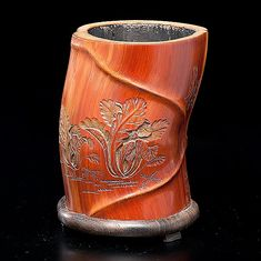 Chinese, early 20th century. A bamboo brush pot carved with plants, lacquered interior, fitted rosewood base, inscription on one side; overall ht. 6.25 in.