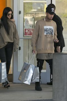 Tyga wearing  Adidas Yeezy Season 1 950 Boots, Amiri MX2 Jeans, Last Kings Last Kings Records Logo Cap, Fear of God We're Here to Help Crewneck in Camel