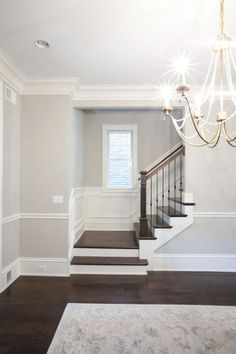 PLD Custom Home Builders - staircase and railing. Love the soft gray paint colour with the dark wood flooring.
