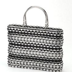 This stylish 11 by 8 inch bag made of strips of soda pull tabs and tire inner tube has two solid metal handles and a zipper closure. The black cotton lining has an internal zip pocket. Meet the Artisa