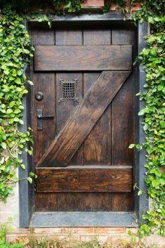 Petit style espagnol sombre colorées porte en bois à jardin secret avec fenêtre râpé