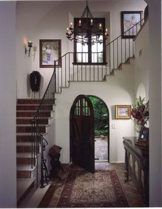 Decorative wrought iron. One prominent feature is the use of wrought iron throughout the home. This grand foyer accommodates a Spanish-style chandelier, wall sconces and stair railing.