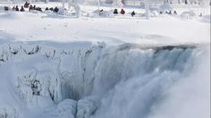Visitors look over masses of ice formed around the American Falls, photographed from across the Niagara River in Niagara Falls, Ontario, Canada,