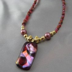 Gorgeous multi-layered red, pink and copper colored dichroic glass pendant on a hand-strung necklace of red stone and glass beads with gold accents.  Only $47.99!