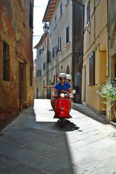 Summer days on a vespa in a tuscan village street.