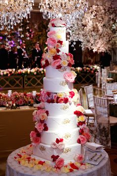Wedding cake was decorated with a white lace design and the couple's monogram in gold. Fresh roses in shades of pink, red, and yellow adorned each tier.