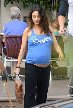 Team spirit: Mila Kunis displayed her growing baby bump in a blue Dodgers tank top at a ba...