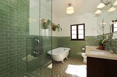 Green tile. footed tub. dark cabinets. light countertops. glass shower.