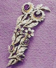 Queen Elizabeth II:  The brooch is a miniature flower bouquet with seven amethyst buds surrounded by white and yellow gold ferns and grasses, with a central group of twelve freshwater mauve-tinted pearls from the River Tay.