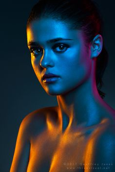 The mix of color in this image provides an almost alien quality to the model. At the front of her body there is a contrast between warm and cool light, while a the back of her body is a strong saturated pink color. The light appears to be hitting her body in a striped pattern suggesting that the sources come from different angles.