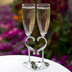 Linked Love Flutes Nickel-plated stems with heart-shaped design, rhinestone accents and interlocking heart base on these champagne wedding toasting glasses.