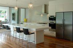 isla de cocina blanca con sillas negras