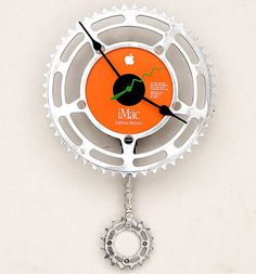 Unusual wall clock made from Apple iMac software restore disk and recycled bicycle parts.