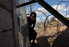 A Zimbabwean immigrant  illegally crosses the border into South Africa. Photo: John Moore/Getty IMages