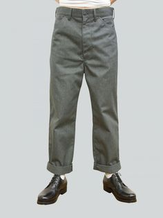 These grey wide-legged trousers feature a zip fastening, adjustable width and a large patch pocket at back. 65% polyester, 35%…
