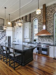 I love this loft kitchen. Love the gorgeous wood floors, the brick wall, the black island with black granite counters.