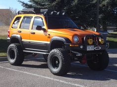 Orange Lifted Liberty Kj With Mud Tires And Kc Lights Pretty