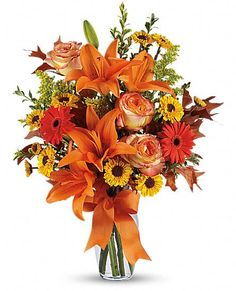 Burst of Autumn Flowers: A mix of fresh flowers such as Asiatic lilies, Viking spray chrysanthemums, roses and a miniature gerbera - in shades of orange and yellow - is arranged with preserved oak leaves in a clear glass vase adorned with an orange satin ribbon.