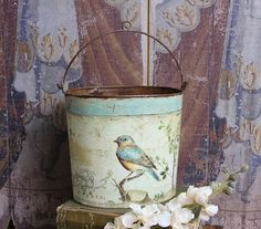 Tin bird bucket.        I bet you could decopauge  paper or vintage cards on an old bucket or peat pots.  fill with easter basket items