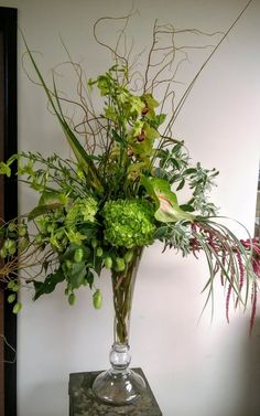 extravagant green, white and cranberry floral arrangement.  includes hydrangeas, orchids, snow on the mountain, hanging amaranths, and hopps
