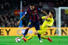 Dani Alves of FC Barcelona is brought down by Luciano Vietto of Villarreal CF during the Copa del Rey Semi-Final first leg match between FC Barcelona and Villarreal CF at Camp Nou on February 11, 2015 in Barcelona, Catalonia.