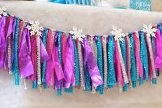 This 5 foot hand tied fabric garland is made up of four shimmery and sparkly fabrics in shades of teal, silver, fuschia, and purple. A set of 6