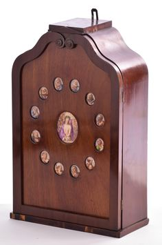 """Selkirk Auctioneers  CABINET WITH OVAL PORCELAIN PLAQUE COLLECTION.  Nineteenth / 20th century. Wall mounted architectural cabinet, the door inset with 12 small painted oval plaques, surrounding a larger oval plaque of Jesus. Cabinet 20.75""""h. 13""""w. Large plaque 3.3""""h. 2.8""""w. Small plaques 1.4""""h. 1.2""""w.  Estimate $ 200-400"""