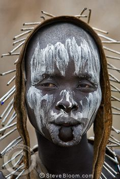 Mursi tribeswoman with unusual headdress, painted face and lower lip stretched to accommodate lip plate. Omo Delta, Ethiopia, Africa.