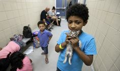 Keedan Garcia, eight, holds his kitten as he waits with his family to be evacuated after the outer bands of Hurricane Harvey are felt in Corpus Christi, Texas
