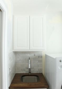 Just a Girl: Chic laundry room with white stock cabinets with wood countertop and marble subway tile ...