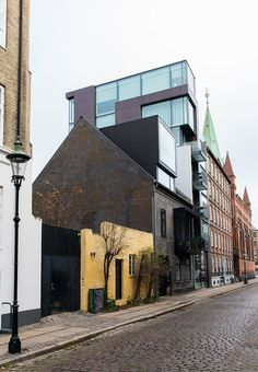 7 story and 7 meters wide glass house in an old street of Copenhagen. In addition to glass, the facade is made up of tombac, which is a copper alloy that patina over the years and which will act as a counterpart to the nearby corroded copper roofs.