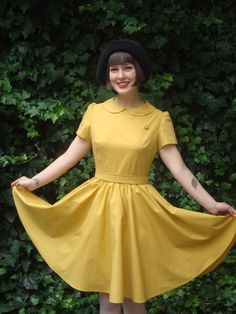 ren's dresses features include a full gathered circle skirt, a beautiful vintage button sewn onto the left of the bodice, Peter Pan collar, short sleeves with slight gathering, fitted bodice, back invisible zip, waist sash and finishing just above the knee.