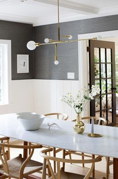 dark grey wallpaper above white panelling, mid century table and light fixture, wishbone chairs