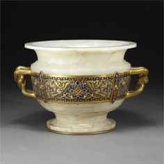 Ferdinand Barbedienne\n1810-1892\nAn Islamic style gilt-bronze, champlevé enamel and onyx centerpiece\nParis, circa 1885, Decorated in the round with an enamelled band of arabesques and scrollwork, signed F. BARBEDIENNE.\nHeight 10 1/2 in.; width 16 3/4 in.\n26.5 cm; 42.5 cm