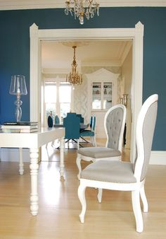 Teal dining room with grey and white chairs