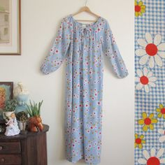 D E S C R I P T I O N: Loose & flowy 1960s full length nightgown in a soft blue gingham with colorful daisy daisies printed allover. Gathered