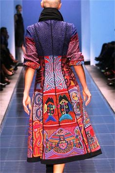 This coat comes from designer Amelia Toro who likes to incorporate traditional Panamanian molas in her creations.   Molas are considered a type of reverse appliqué formed from multiple layers of fabric that are cut into intricate patterns. Molas were the mainstay of the traditional outfits of a Kuna women, two mola panels being incorporated as front and back panels in a blouse.  See more of the designer's work on her website at http://ameliatoro.com/NA-AS/index.php/en/