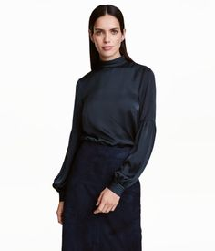 Dark blue. Straight-cut blouse in satin with small stand-up collar decorated with cutwork stitching. Opening and concealed buttons at back of neck. Long