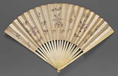 1775-1790, England - Fan with painted gray-white paper leaf - Small painted and silvered sprays of flowers in manner of Spitalsfield silks; light brown paper band at top. Carved ivory sticks, blades form decorative motif when closed. Mother-of-pearl rings on rivet.