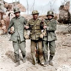 A wounded British soldier being assisted by two of his German captors. 1917, Western Front.