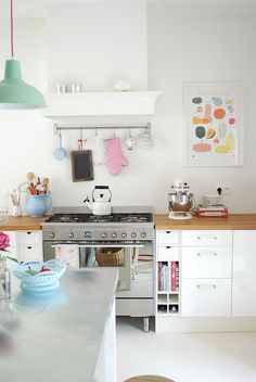 Though the whimsical touches are fun, what I really love is the storage next to the stove.  Those little bitty drawers and small cookbook shelf are precious.
