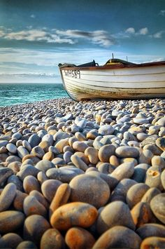 The image is focused more on the pebbles and the boat and bright ocean in the background is pretty.