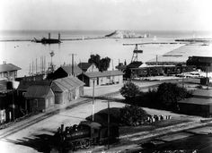 (1905) - View looking over a portion of San Pedro, toward Deadman's Island, and the beginning harbor. Building at extreme left is the Southern Pacific depot. In the distance is a dredge at work along the breakwater.