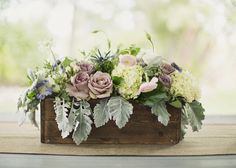 Love the mauve roses and dusty miller in this wooden centerpiece flower box. Photography: Alixann Loosle Photography - alixannlooslephotography.com Floral Design: Branches Event Floral - branchesfloraldesign.com