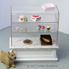 A dollhouse scale shop display case with a 'glass' top made from bent acrylic sheet.