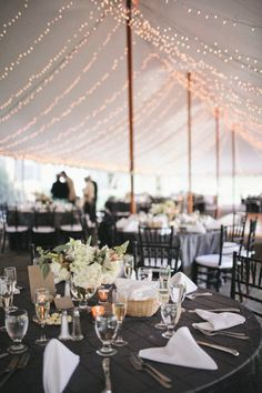dark gray tablecloth, white centerpiece,  black chairs, white cushion