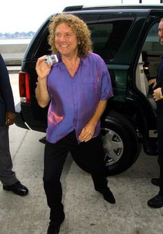 Robert Plant takes pictures of the media as he arrives at General Motors world headquarters August 22, 2002 in Detroit, Michigan for Cadillac's 100th anniversary