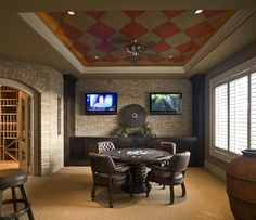 Traditional dining room converted into a man cave with the gold patterned carpet, round poker table, leather tufted chairs and a checker pattern on the ceiling. That massive wine cellar in back isn't a bad touch either.
