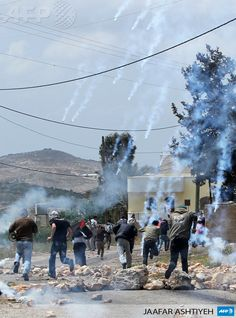 Kfar QADDUM: Palestinian protesters run away from tear gas canisters fired by Israeli security forces during clashes following a protest against the expropriation of Palestinian land by Israel in the village of Kfar Qaddum near Nablus in the occupied West Bank on April 19, 2013. AFP PHOTO / JAAFAR ASHTIYEH April 19, Running Away, Canisters, Middle East, Israel, Fire, Mountains, Container, Bergen