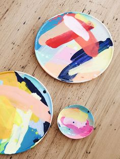 Large colourful paint strokes randomly brushed onto white ceramic make vibrant dinnerware. Image via thedesignfiles